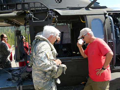 Ops leader and helicopter pilot reviewing plans with victim via cell phone